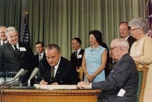 Lyndon B. Johnson signs legislation amending the Social Security Act.